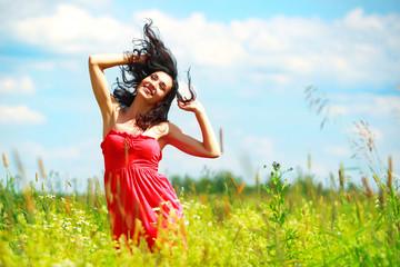 Happy beautiful woman dancing in meadow
