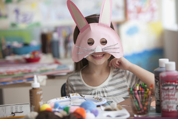 Caucasian girl making rabbit mask
