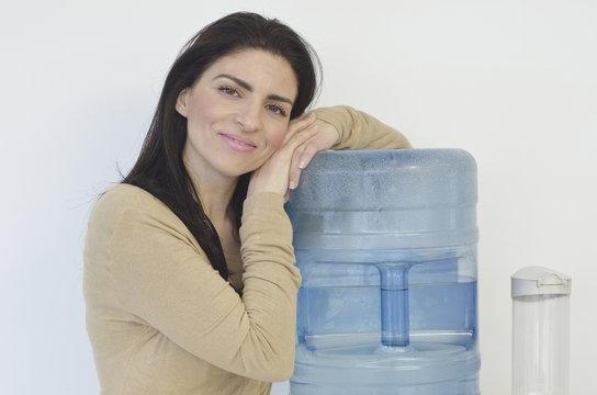 Hispanic businesswoman leaning on water cooler