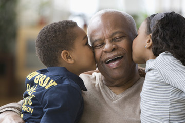 Grandchildren kissing grandfather
