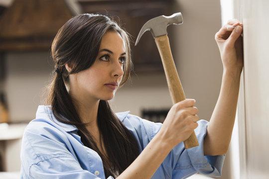 Caucasian woman hammering nail into wall