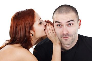 Woman whispering into man`s ear