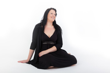 Young woman in black dress sitting on the floor
