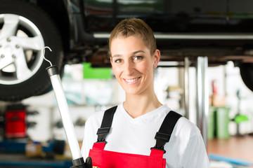Auto Mechanikerin arbeitet an Auto auf Hebebühne