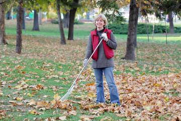 Autumn, woman raking leaves and smiling