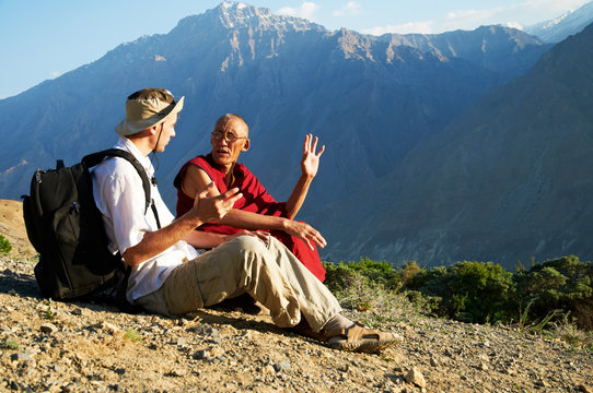 European tourist talks with the Tibetan lama in mountains