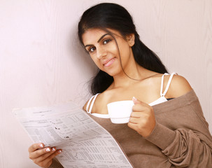 Pretty young woman in bedroom with coffee