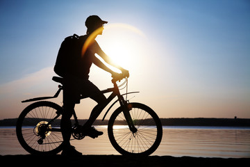 cyclist on road at sunset