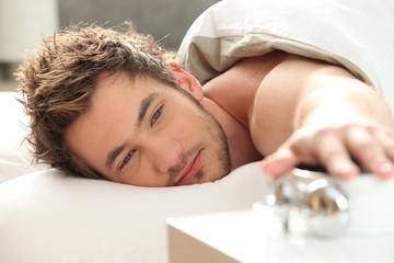 Man turning off alarm clock