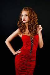Beautiful, daring red-haired girl in a red dress on a black back