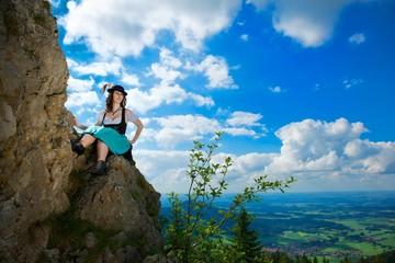 Junge Frau im Dirndl auf Felsen
