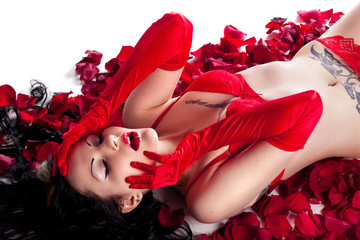 girl with tattoos in red lingerie in the petals of red roses