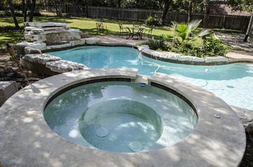 Upscale backyard hottub and swimming pool with flora landscaping