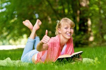 liegende Frau mit Buch zeigt Top Daumen
