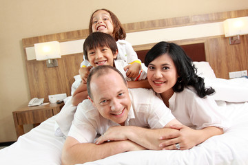 happy family on white bed