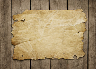 Old paper sheet at grunge wooden background