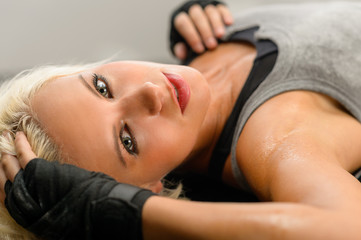 Woman kickboxer in black relax on floor