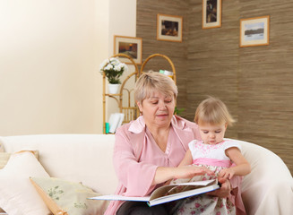 The grandmother reads to the grand daughter the book on a sofa