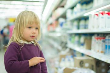 Adorable girl in milk department in supermarket