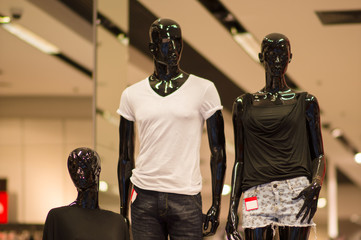 T-shirts and shorts on black mannequins in mall