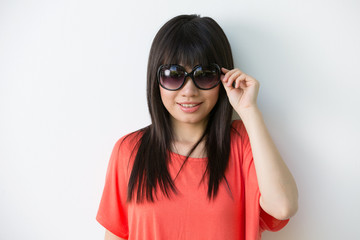 Cool Asian woman leaning against a wall with sunglasses.
