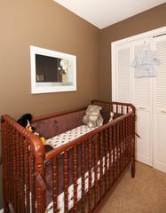 Cherry wood baby crib in nursery interior.