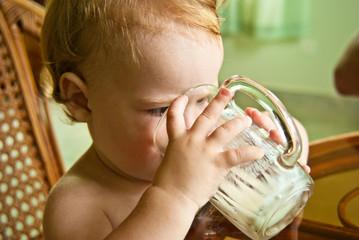 Child 1,5 years old drink mug of yoghurt