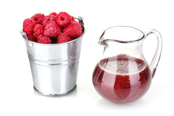 Raspberries in metal bucket and jug with jam isolated on white