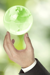 Businessman holding green globe - ecology or environment concept