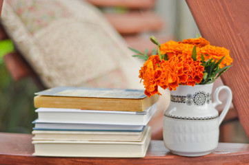 Books, and marigolds in a vase stock image