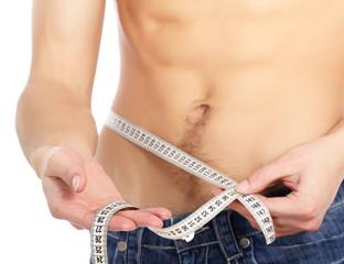 A muscular man measuring his waist