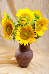 Bouquet of sunflowers in a clay vase.
