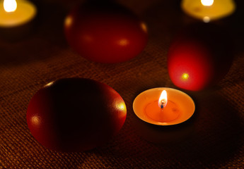 Closeup of rounded candle placed between three red eggs