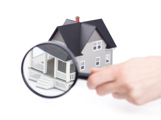 Real estate concept - hand holding magnifying glass