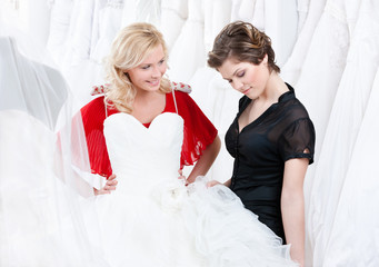 Young girl is thinking over a wedding gown