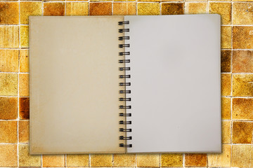 Blank notebook on yellow tiles background