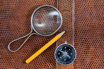 Snake leather texture with magnifying glass, compass and pencil