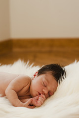 Vertical pic of a sweet newborn sleeping and dreaming