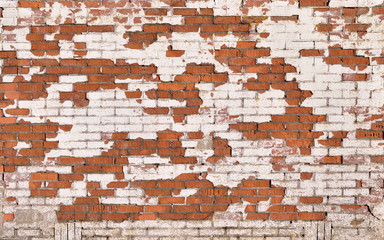 Red brick wall with severe damaged white stucco