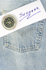 blue jean with paper (success)and compass on the pocket.