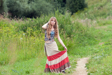 The woman of hippie in a skirt costs near a track