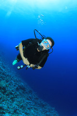 Female Scuba Diver in clear blue ocean