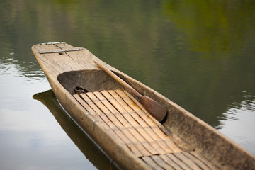 Wooden canoe  with an oar on the calm lake water