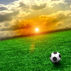 A fine green meadow with a soccer ball on it. All on sky sunset