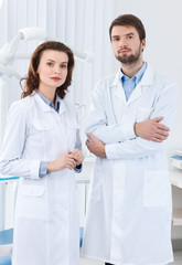 Dentist and his assistant wait the patient, white background