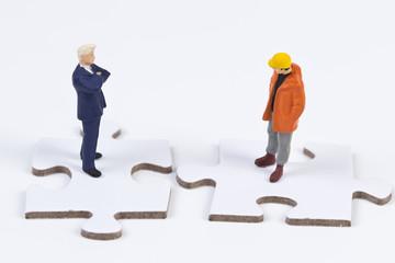 Zwei Miniaturfiguren auf einem Puzzle