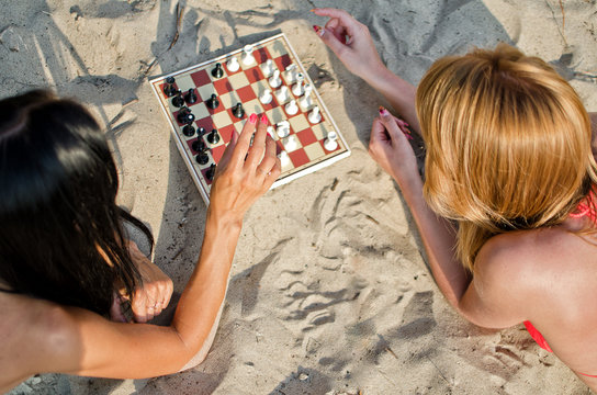 Two girls playing chess on the beach