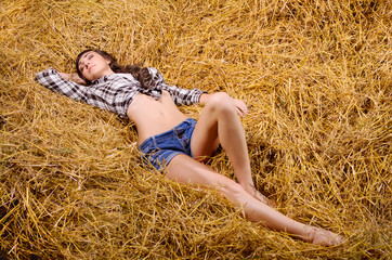 Woman lying on haystack