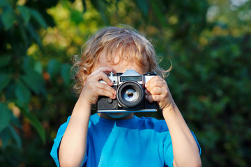 Little blond boy with a camera shoots you outdoors