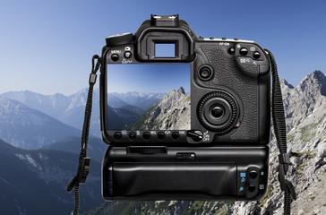 Spiegelreflexkamera mit den Alpen im Hintergrund